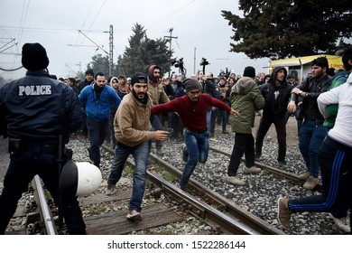 Idomeni, Greece - February 29, 2016. Refugees break a police blockade at the makeshift refugee camp of Idomeni in order to approach the Greek Macedonian border.