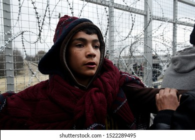 Idomeni, Greece - February 29, 2016. A young refugee man stands next to a border fence during a protest at the Greek Macedonian border.