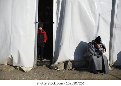 Idomeni, Greece - January 15, 2016. A refugee boy watches from inside a tent as a man sits outside at the makeshift refugee camp of Idomeni at the Greek Macedonian border.