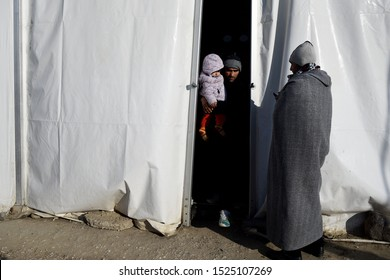 Idomeni, Greece - January 15, 2016. Refugees stand at the entrance of a large tent at the makeshift refugee camp of Idomeni at the Greek Macedonian border.