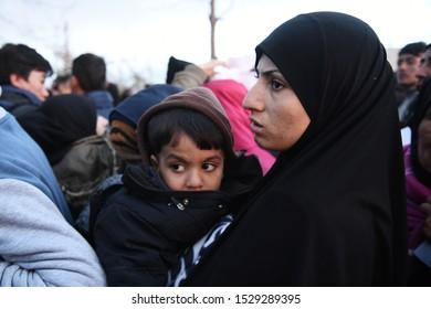 Idomeni, Greece - January 15, 2016. A refugee woman with her son wait to cross the Greek-Macedonian border.