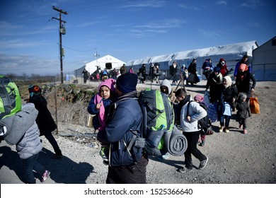 Idomeni, Greece - January 27, 2016. A man holds his daughter as refugees approach in order to cross the Greek Macedonian border.