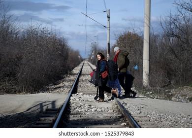 Idomeni, Greece - January 27, 2016. A refugee family walk over a railroad as they cross the Greek-Macedonian border.