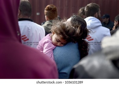 Idomeni, Greece - March 2, 2016. A refugee girl sleeps in the arms of her mother at the makeshift refugee camp of Idomeni, at the Greek - Macedonian border.