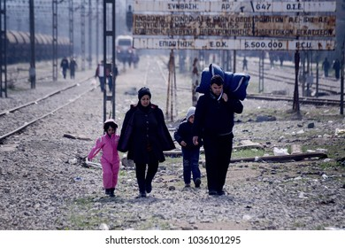 Idomeni, Greece - March 2, 2016. A family of refugees walk next to the rail tracks, at the makeshift refugee camp of Idomeni, at the Greek Macedonian border.