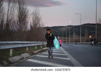Idomeni, Greece - March 2, 2016. A refugee girl carries her belongings as refugees approach the Greek Macedonian border.