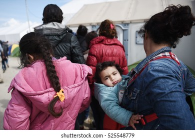 Idomeni, Greece - March 2, 2016. A refugee woman carries her child in the makeshift refugee camp of Idomeni, at the Greek - Macedonian border.