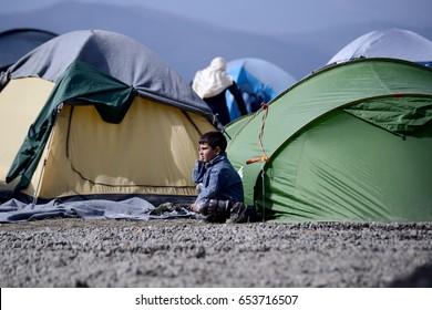 Idomeni, Greece - March 2, 2016. A boy sits outside a tent, at the makeshift refugee camp of Idomeni, at the Greek - Macedonian border.