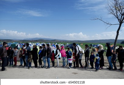 Idomeni, Greece - March 2, 2016. Refugees wait in line to receive food, at the makeshift refugee camp of Idomeni, at the Greek - Macedonian border.