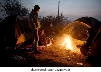 Idomeni, Greece - March 4, 2016. A group of Syrian refugees are warming up around a bonfire outside their tents inside the makeshift refugee camp of Idomeni.