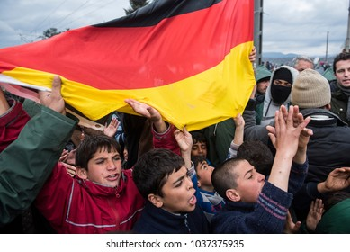 Idomeni, Greece - March 9, 2016. Refugee boys hold a German flag, as refugees and migrants demonstrate demanding for the European Union borders to open, in the refugee camp of Idomeni.
