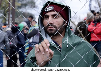 Idomeni, Greece - March 9, 2016. A migrant man watches behind a fence inside the makeshift refugee camp of Idomeni at the Greek Macedonian border.