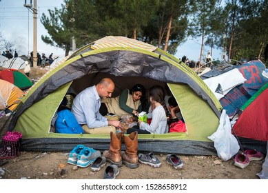 Idomeni, Greece - March 9, 2016. A family of Syrian refugees sit inside their tent at the makeshift refugee camp of Idomeni at the Greek-Macedonian border.