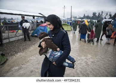 Idomeni, Greece - March 9, 2016. A refugee woman carries her child, as around 10000 refugees and migrants remain stranded at the Greek Macedonian border, at the makeshift refugee camp of Idomeni