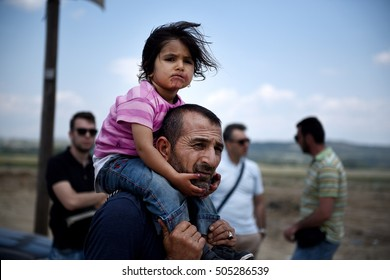 Idomeni, Greece - May 26, 2016. A Syrian man carries his daughter, as refugees abandon the makeshift camp of Idomeni in northern Greece, after the evacuation operation by the Greek police.