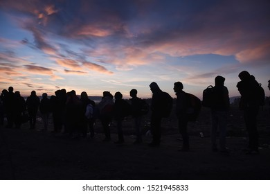 Idomeni, Greece - October 23, 2015. Silhouettes of refugees are seen as they wait to cross the Greek Macedonian border.