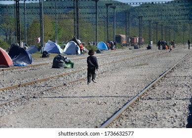 Idomeni/Greece-April 15, 2016: Children playing on railway tracks in transit refugee/migrant camp at the Greek-North Macedonian border. Families stuck on their way to Western Europe.