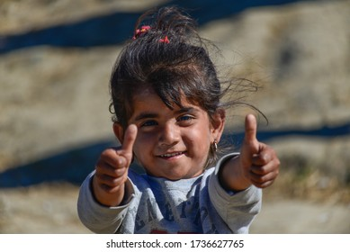 Idomeni/Greece-April 15, 2016: Girl showing thumbs up in transit refugee/migrant camp at the Greek-North Macedonian border. Families stuck on their way to Western Europe.