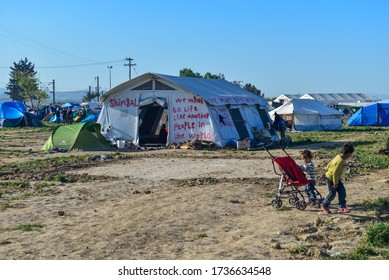 Idomeni/Greece-April 15, 2016: Inscription on the tent and kids playing in transit refugee/migrant camp at the Greek-North Macedonian border. Families stuck on their way to Western Europe.