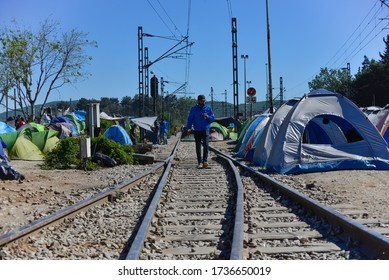 Idomeni/Greece-April 15, 2016: Man walking on railway tracks in improvised tent city. Difficult life conditions in transit refugee/migrant camp at the Greek-North Macedonian border.