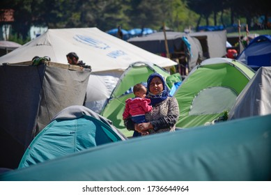 Idomeni/Greece-April 15, 2016: Woman with a baby in transit refugee/migrant camp at the Greek-North Macedonian border. The European refugee and migration crisis.