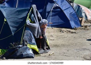 Idomeni/Greece-April 15, 2016: Worried woman looking out from her tent in transit refugee/migrant camp at the Greek-North Macedonian border. The European refugee and migration crisis.