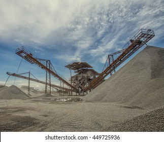 Idustrial background with working gravel crusher ,stone crusher in a quarry. mining industry.