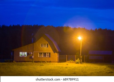 idyll of country: overnight, night light, cozy cottage surrounded by meadows at edge of forest