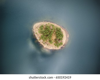 Idyllic aerial view with a secluded island in the middle of the lake with no borders of coastline visible.