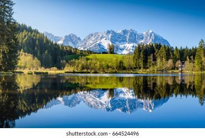 Idyllic alpine scenery, snowy mountains mirroring in a small lake, Kitzbuehel, Tyrol, Austria