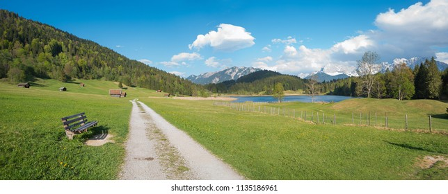 idyllic bavarian summer landscape with walkway to lake gerold and bench