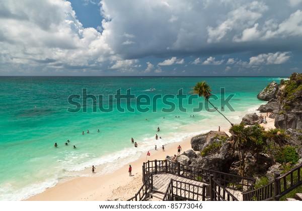 Idyllic beach of Tulum with people enjoying lagoon water - Mexico