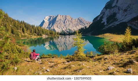 idyllic blue lake seebensee in the austrian alps with view to famous zugspitze, reflecting in the water. young mountaineering woman sitting at the lake shore.