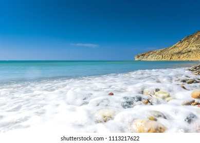 Idyllic calm tropical beach with turquoise sea water and pebble stones