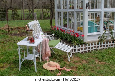 Idyllic Edwardian Era Springtime Scene of White Chair and table set up for Champagne and strawberries in Garden