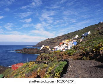 idyllic fishing village on Tenerife El Pris, stretches with colorful houses up the slope, directly on the Atlantic Ocean with picturesque surroundings and white clouds in the blue sky