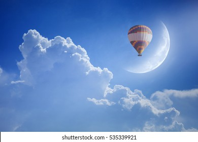 Idyllic heavenly background - colorful hot air balloon rise up into blue sky above white clouds to new moon. Dream come true concept