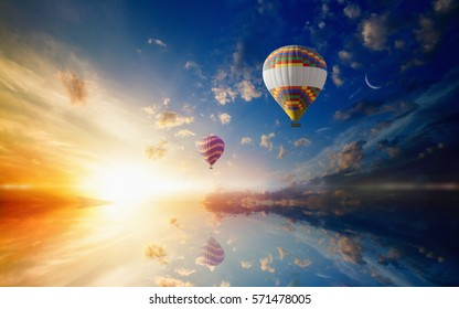 Idyllic heavenly background - two colorful hot air balloons flies in sunset sky above calm sea. Bright sun, glowing horizon and crescent in blue sky
