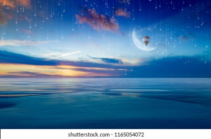 Idyllic heavenly picture - colorful hot air balloon in sunrise sky with crescent above serene sea. Dream come true concept. Elements of this image furnished by NASA