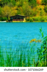 Idyllic isolated cabin on a lake, on a sunny summer day with a boat in the water in front of it