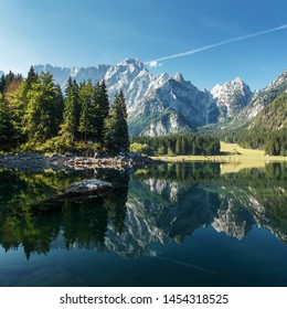 Idyllic landscape in the Alps with calm mountain lake and majestic Mangart mount under sunlight in summer. Amazing nature scenery with reflections. Fusine lake. Italy. postcard. picture of wild area