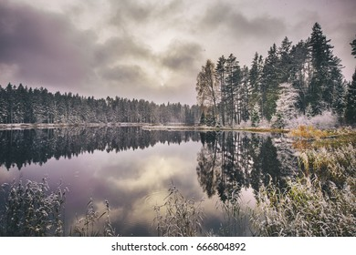 Idyllic landscape with lake and forest in early Winter.