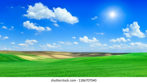 Idyllic landscape, sun shining over green rolling fields, in the background blue sky and white clouds