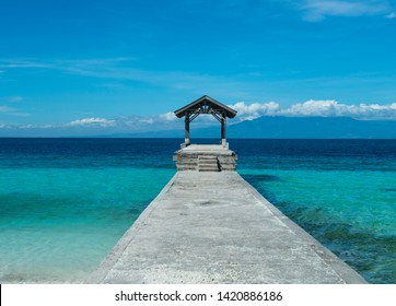 idyllic looking jetty with a cottage stretching towards the turquoise sea of talikud island davao philippines.
