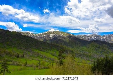 Idyllic mountain landscape with clouds and lush greens