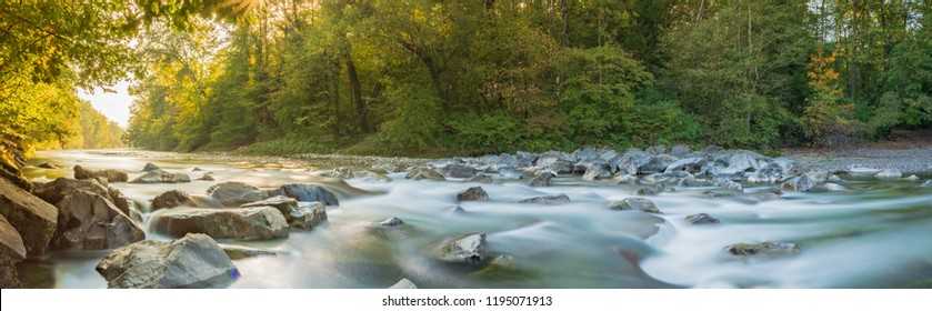 Idyllic panorama landscape in autumn on river in Forest with warm sunlight trough Trees