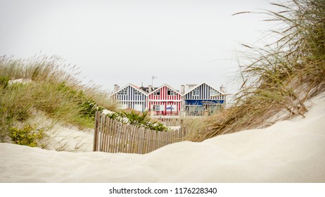 Idyllic and quaint beach houses seen from beach dunes. Beach houses with colorful stripes from Costa Nova, Portugal.