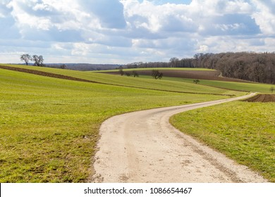 idyllic and rural panoramic scenery with fields and meadows including a field path in Hohenlohe, a area in Southern Germany at early spring time time