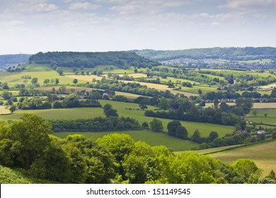 Idyllic rural view of gently rolling patchwork farmland and villages with pretty wooded boundaries, in the beautiful surroundings of the Cotswolds, England, UK.