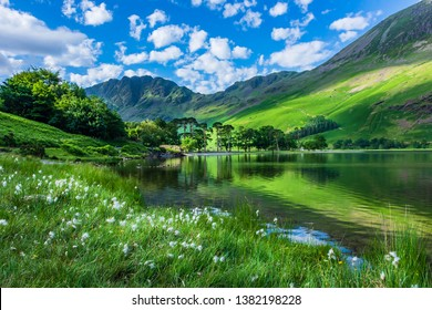 Idyllic scenery of English Lake District in springtime.Trees and grass growing on lakeshore, green hill reflecting in lake water.Sunlight kissing mountain slope in background.Majestic landscape scene.